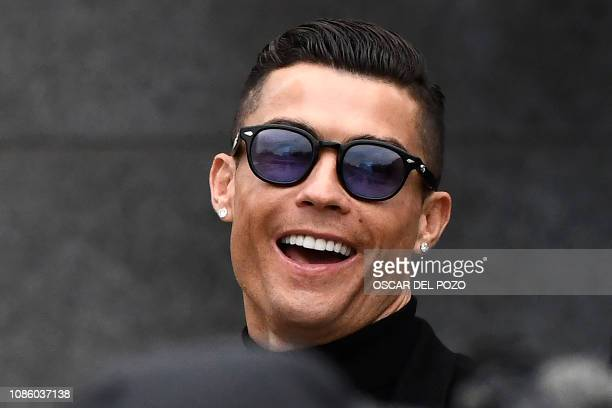 Juventus' forward and former Real Madrid player Cristiano Ronaldo laughs as he leaves after attending a court hearing for tax evasion in Madrid on...