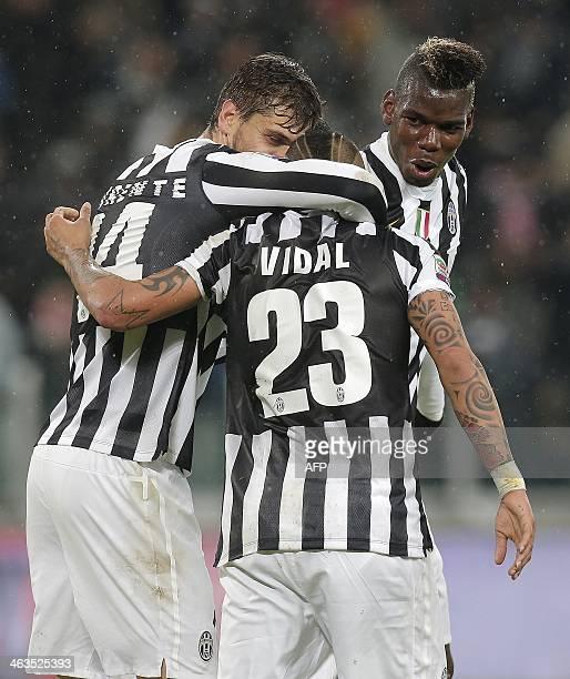 Juventus' forward Arturo Vidal is congratulated by his teammates Paul Pogba and Fernando Llorente after scoring a goal during the Italian Serie A...