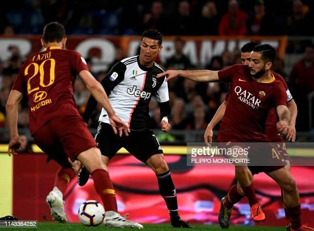 Juventus forward Cristiano Ronaldo vies with Roma defenders Federico Fazio of Argentina and AS Roma Greek defender Konstantinos Manolas during the...