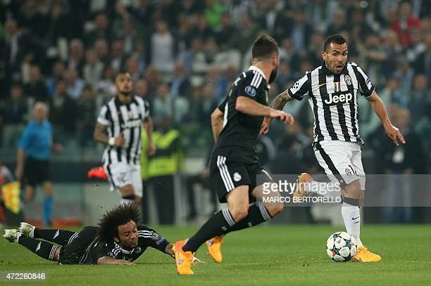 Juventus' forward from Argentina Carlos Tevez vies with Real Madrid's defender Dani Carvajal and Real Madrid's Brazilian defender Marcelo during the...