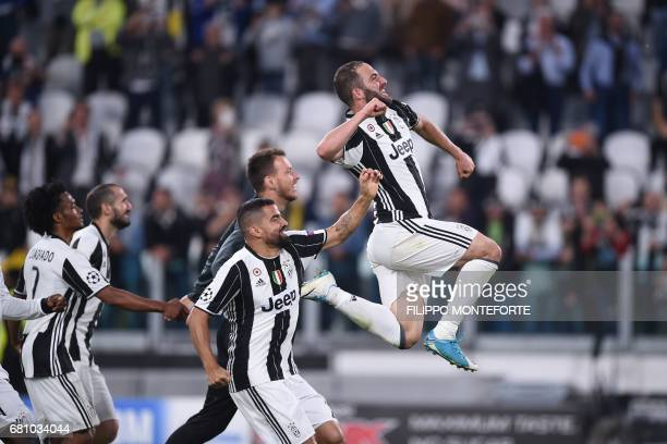 TOPSHOT Juventus' forward from Argentina Gonzalo Higuain celebrate with teammates at the end of the UEFA Champions League semi final second leg...