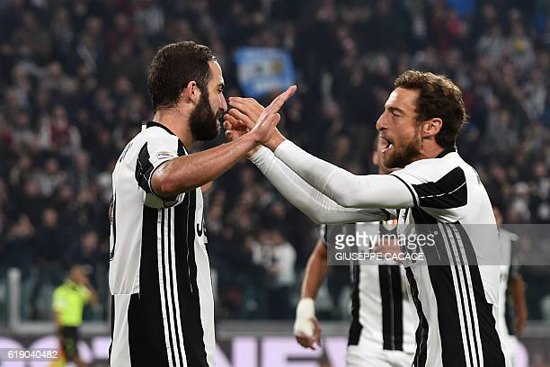 Juventus' forward from Argentina Gonzalo Higuain celebrates with Juventus' midfielder from Italy Claudio Marchisio after scoring a goal during the...