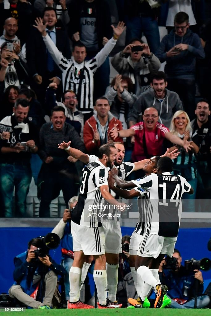 Juventus' forward from Argentina Gonzalo Higuain (C) celebrates with teammates after scoring during the UEFA Champion's League Group D football match Juventus vs Olympiacos on September 27, 2017 at the Juventus stadium in Turin. / AFP PHOTO / Miguel MEDINA