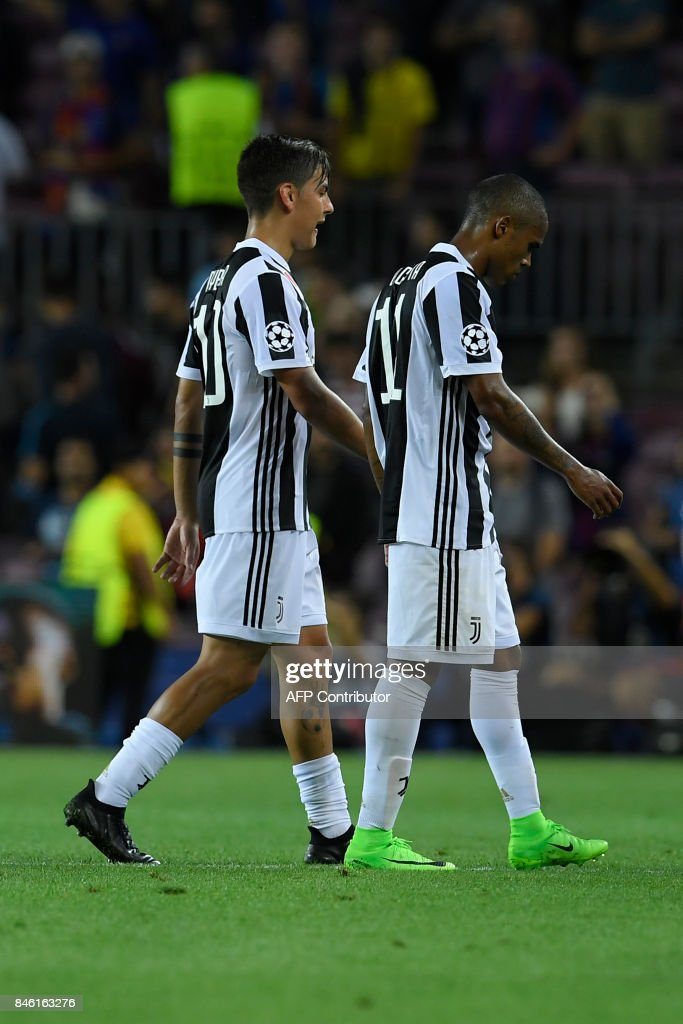 Juventus' forward from Argentina Paulo Dybala (L) and a teammates leave the pitch at the end of the UEFA Champions League Group D football match FC Barcelona vs Juventus at the Camp Nou stadium in Barcelona on September 12, 2017. /