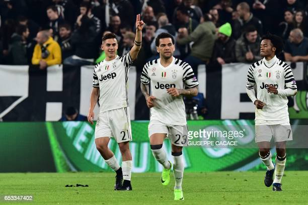 Juventus' forward from Argentina Paulo Dybala celebrates with teammates Juventus Defender from Brazil Dani Alves and Juventus' forward from Colombia...