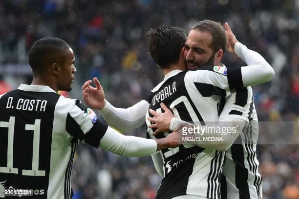 Juventus' forward from Argentina Paulo Dybala celebrates with teammates Juventus' forward from Brazil Douglas Costa and Juventus' forward from...