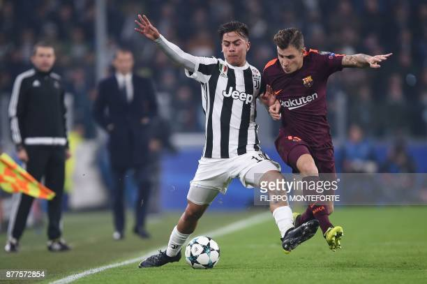 Juventus' forward from Argentina Paulo Dybala fights for the ball with Barcelona's French defender Lucas Digne during the UEFA Champions League Group...