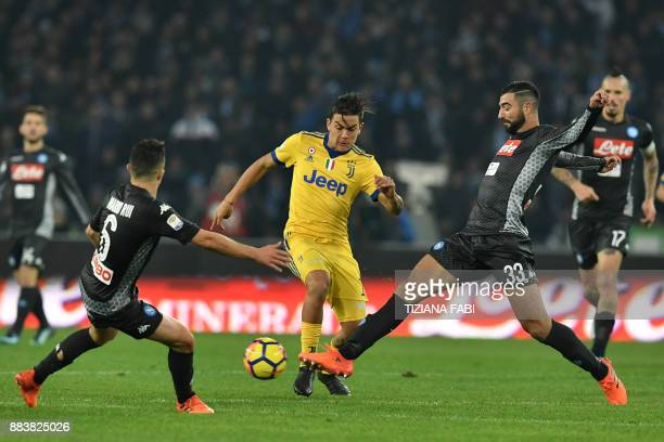 Juventus' forward from Argentina Paulo Dybala fights for the ball with Napoli's Portuguese defender Mario Rui and Napoli's defender from Spain Raul...