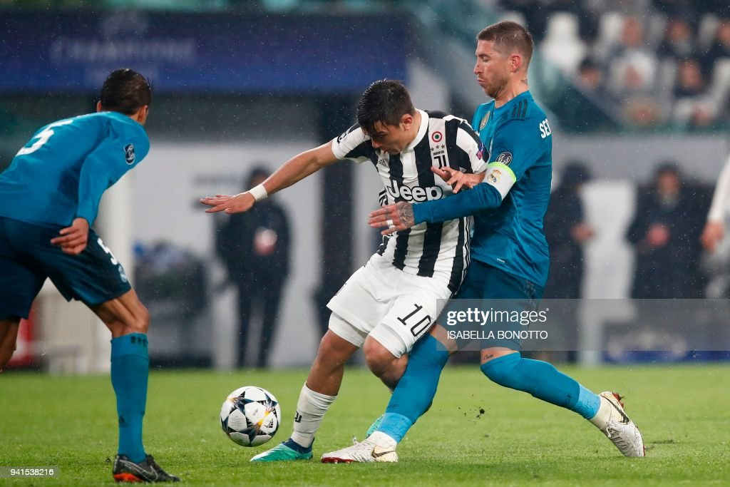 Juventus' forward from Argentina Paulo Dybala (C) fights for the ball with Real Madrid's Spanish defender Sergio Ramos (R) during the UEFA Champions League quarter-final first leg football match between Juventus and Real Madrid at the Allianz Stadium in Turin on April 3, 2018. Ronaldo scores twice as Real Madrid beat Juventus 3-0. / AFP PHOTO / Isabella BONOTTO