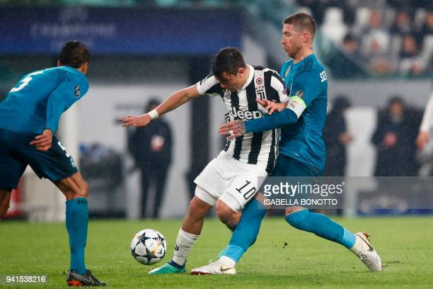 Juventus' forward from Argentina Paulo Dybala fights for the ball with Real Madrid's Spanish defender Sergio Ramos during the UEFA Champions League...