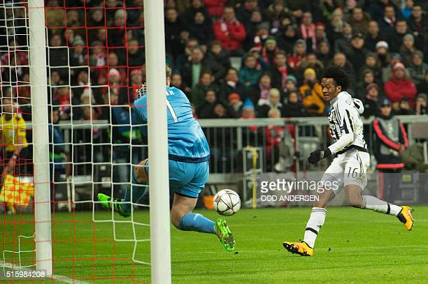 Juventus' forward from Colombia Juan Cuadrado has a shot on Bayern Munich's goalkeeper Manuel Neuer's goal during the UEFA Champions League Round of...