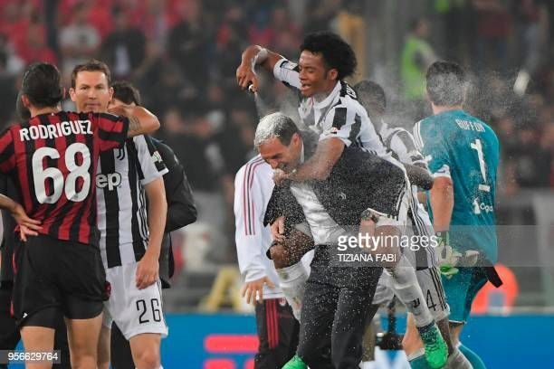 TOPSHOT Juventus' forward from Colombia Juan Cuadrado sprays shaving cream on the head of Juventus' coach from Italy Massimiliano Allegri after...