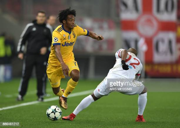 Juventus' forward from Colombia Juan Cuadrado vies for the ball with Olympiacos' Brazilian forward Seba during the UEFA Champions League group D...