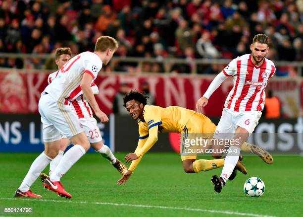 Juventus' forward from Colombia Juan Cuadrado vies for the ball with Olympiacos' Belgian defender Bjorn Engels and Olympiacos' midfielder Panagiotis...