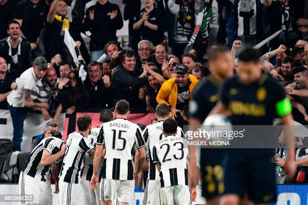 TOPSHOT Juventus' forward from Croatia Mario Mandzukic celebrates with fans and teammates after scoring during the UEFA Champions League semi final...