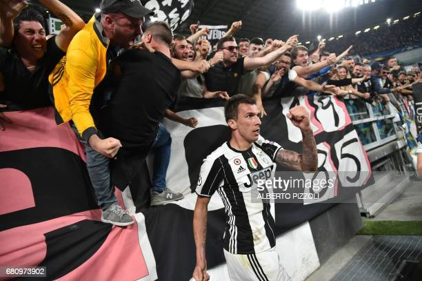 TOPSHOT Juventus' forward from Croatia Mario Mandzukic celebrates with fans after scoring during the UEFA Champions League semi final second leg...