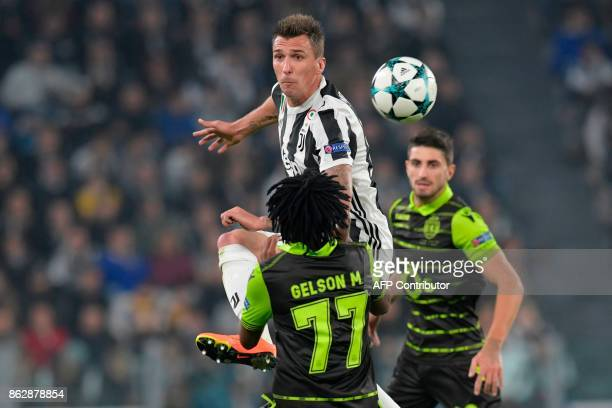Juventus' forward from Croatia Mario Mandzukic fights for the ball with Sporting's forward Gelson Martins during the UEFA Champions League Group D...