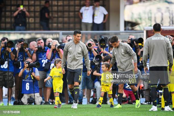 TOPSHOT Juventus' forward from Portugal Cristiano Ronaldo and Juventus' Argentinian forward Paulo Dybala enter the pitch with children prior to the...