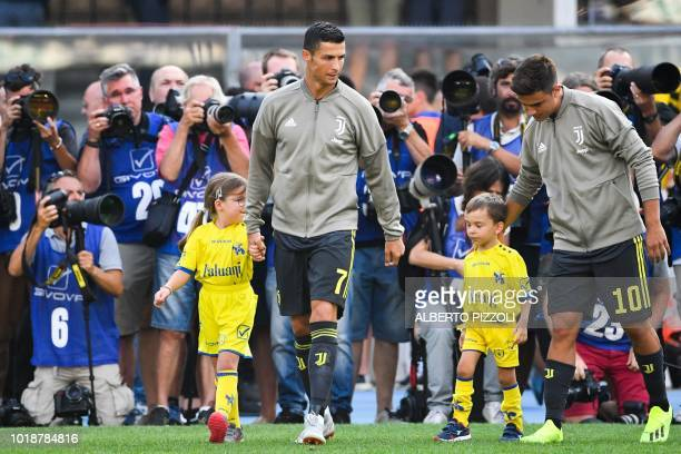 Juventus' forward from Portugal Cristiano Ronaldo and Juventus' Argentinian forward Paulo Dybala enter the pitch with children prior to the Italian...