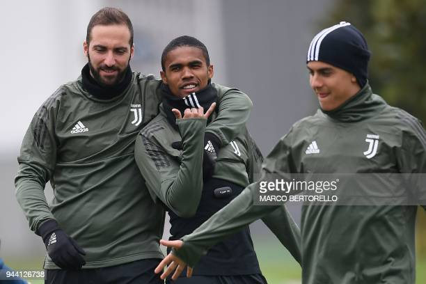 Juventus' forward Gonzalo Higuain from Argentina and Juventus' midfielder Douglas Costa from Brazil attend a training session on the eve of the UEFA...