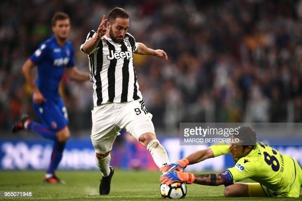TOPSHOT Juventus' forward Gonzalo Higuain from Argentina fights for the ball with Bologna's goalkeeper Antonio Mirante during the Italian Serie A...
