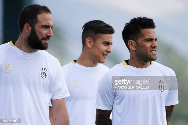 Juventus' forward Gonzalo Higuain from Argentina Juventus' forward Paulo Dybala from Argentina and Juventus' defender Daniel Alves from Brazil take...