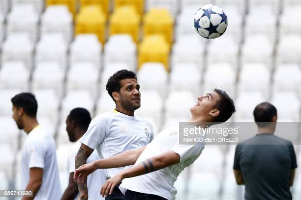 Juventus' forward Paulo Dybala from Argentina and Juventus' defender Daniel Alves from Brazil attend the training session during the Media Day prior...