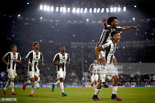 Juventus' forward Paulo Dybala from Argentina celebrates after scoring with Juventus' midfielder Juan Cuadrado from Colombia during the Italian Serie...