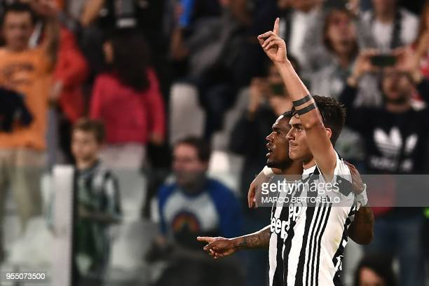 Juventus' forward Paulo Dybala from Argentina celebrates with teammate Juventus' midfielder Douglas Costa from Brazil after scoring a goal during the...