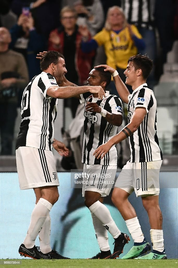 Juventus' forward Paulo Dybala from Argentina celebrates with teammate Juventus' midfielder Douglas Costa from Brazil (C) and Juventus' defender Andrea Barzagli (L) after scoring a goal during the Italian Serie A football match between Juventus and Bologna on May 5, 2018 at the Allianz Stadium in Turin.