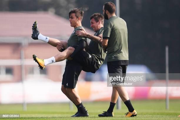 Juventus' forward Paulo Dybala from Argentina jokes with Juventus' forward Mario Mandzukic from Croatia and Juventus' forward from Argentina Gonzalo...