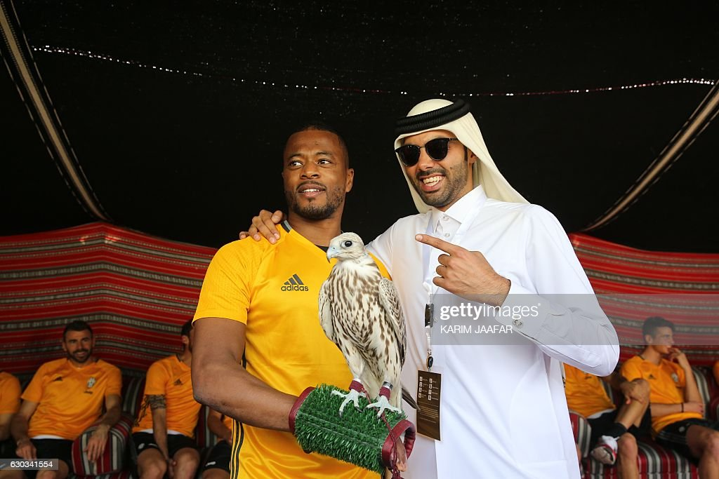 Juventus' French defender Patrice Evra poses with a falcon after a training session in Doha on December 21, 2016, two days before the Italian Super Cup final football match between Juventus and AC Milan in the Qatari capital. / AFP / KARIM