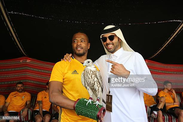 Juventus' French defender Patrice Evra poses with a falcon after a training session in Doha on December 21 two days before the Italian Super Cup...