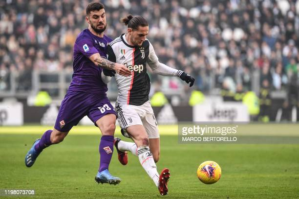 Juventus' French midfielder Adrien Rabiot holds off Fiorentina's Italian forward Patrick Cutrone during the Italian Serie A football match Juventus...