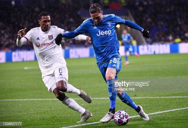 Juventus' French midfielder Adrien Rabiot is challenged by Lyon's Brazilian defender Marcelo during the UEFA Champions League round of 16 firstleg...