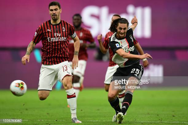 Juventus' French midfielder Adrien Rabiot shoots to open the scoring during the Italian Serie A football match AC Milan vs Juventus played behind...