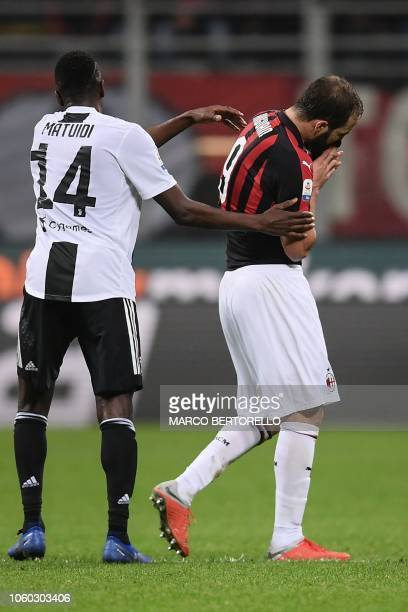 Juventus' French midfielder Blaise Matuidi comforts AC Milan's Argentine forward Gonzalo Higuain as he leaves the pitch after he received a red card...
