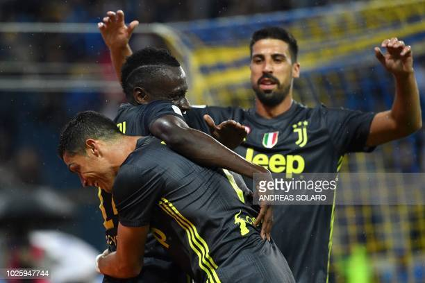 Juventus' French midfielder Blaise Matuidi is congratulated by Juventus' Portuguese forward Cristiano Ronaldo and Juventus' German midfielder Sami...