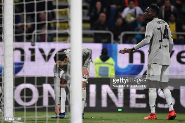Juventus' French midfielder Blaise Matuidi reacts as Juventus' Italian defender Mattia De Sciglio picks up projectiles thrown by Cagliari's fans...