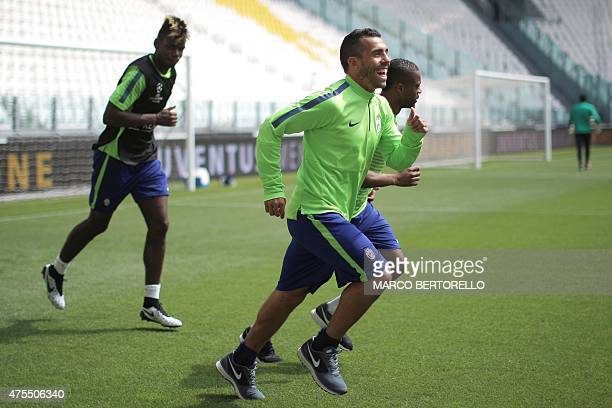 Juventus' French midfielder Patrice Evra jokes with Argentinian forward Alberto Carlos Tevez during a training session on June 1 2015 at the Juventus...