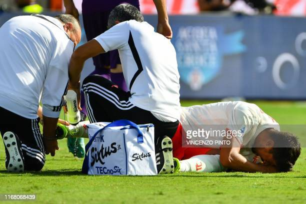Juventus' German midfielder Sami Khedira reacts in pain while being treated by staff medics for an ankle injury during the Italian Serie A football...