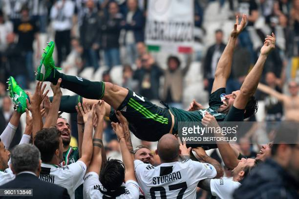 TOPSHOT Juventus' goalkeeper from Italy Gianluigi Buffon is lift in the air by teammates during the victory ceremony following the Italian Serie A...