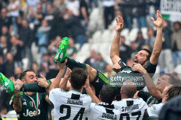 Juventus' goalkeeper from Italy Gianluigi Buffon is lift in the air by teammates during the victory ceremony following the Italian Serie A last...