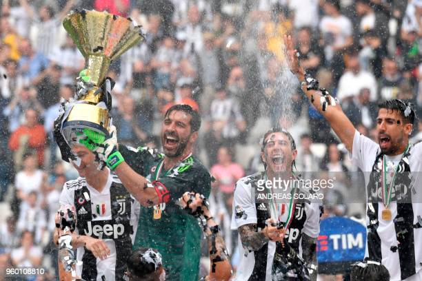 TOPSHOT Juventus' goalkeeper from Italy Gianluigi Buffon rises the trophy during the victory ceremony following the Italian Serie A last football...