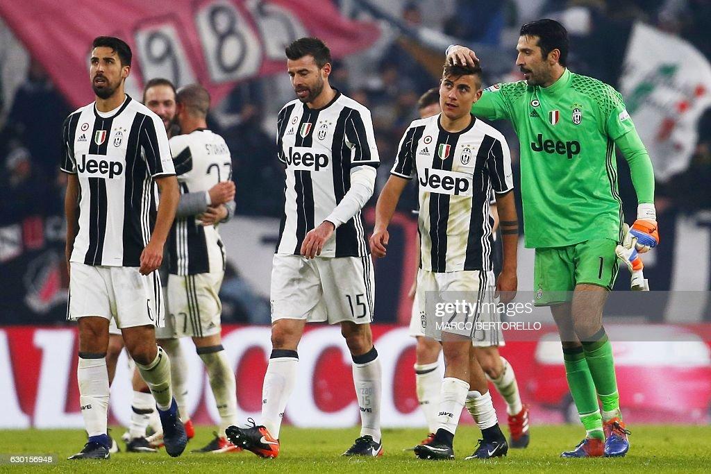 Juventus' goalkeeper Gianluigi Buffon (R) celebrates with Juventus' forward Paulo Dybala (2R) of Argentina at the end of the Italian Serie A football match Juventus vs As Roma on December 17, 2016 at the 'Juventus Stadium' in Turin. / AFP / MARCO