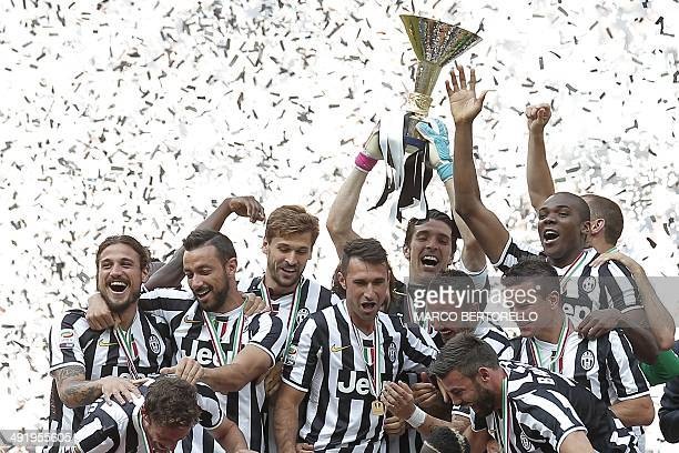Juventus' goalkeeper Gianluigi Buffon holds the trophy as he celebrates with teammates on the podium of the Italian Serie A after their last football...
