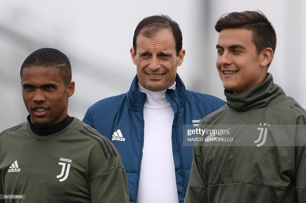 Juventus' head coach Massimiliano Allegri (C), Juventus' Argentinian forward Paulo Dybala (R) and Juventus' Brazilian midfielder Douglas Costa attend a training session on the eve of the UEFA Champions League football match Juventus vs Real Madrid on April 2, 2018 at the Juventus training center in Vinovo. /