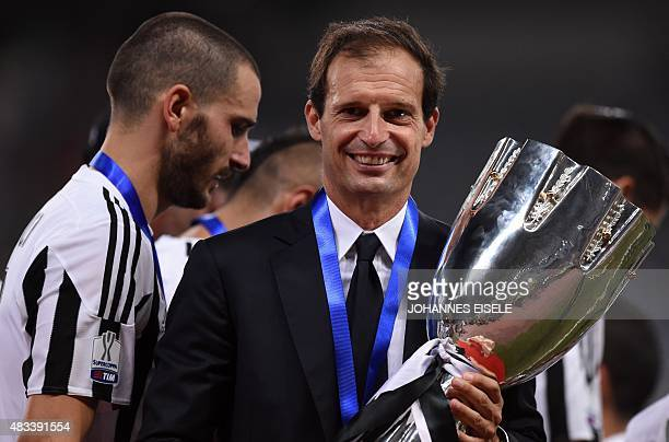 Juventus head coach Massimiliano Allegri poses with the trophy after the Italian Super Cup final football match between Juventus and Lazio in...