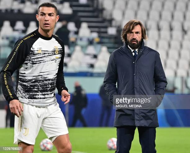 Juventus' Italian coach Andrea Pirlo looks on as Juventus' Portuguese forward Cristiano Ronaldo warms up prior to the UEFA Champions League Group G...