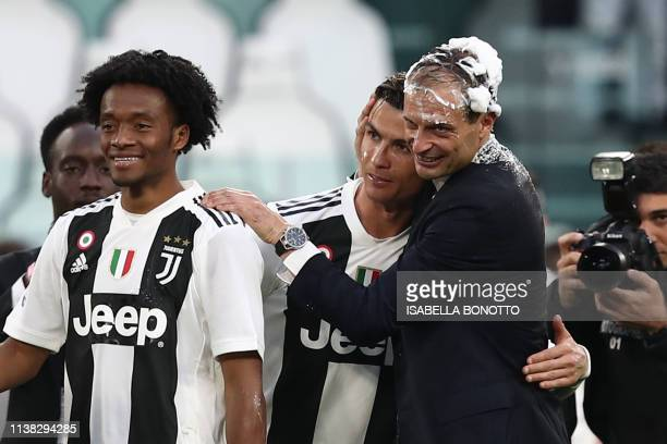 Juventus' Italian coach Massimiliano Allegri embraces Juventus' Portuguese forward Cristiano Ronaldo both with their head covered in foam after...